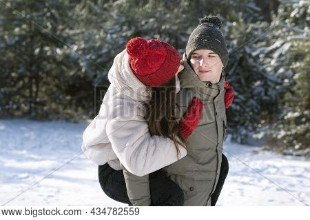 Guy Carries His Girlfriend On His Back. Young Couple Having Fun On Frosty Sunny Day. Winter Forest.