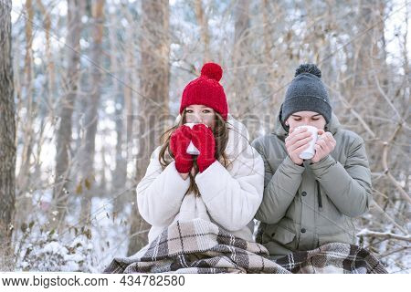 Lovers Drink Tea And Wrapped Themselves In Blanket. Young Couple Had Picnic In Park In Winter