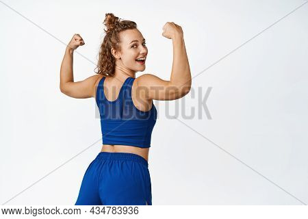 Healthy And Active Sportswoman Showing Muscles, Turn Behind And Laughing, Flexing Biceps On Arms, Fe