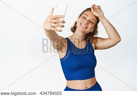 Happy Sportswoman Taking Selfie While Wiping Sweat, Doing Workout And Photographing, Standing In Act