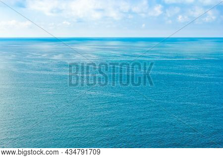 View Of The Calm Sea And Small Clouds In The Distance