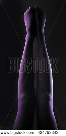 Women Legs In Violet Tights, Raised Up Over Black Background.