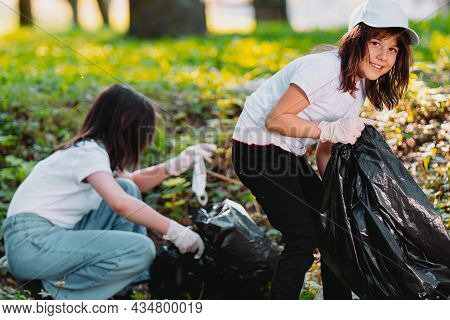 Two Nice Girls Spending Their Time In Voluntary Mission Outdoors In Gathering Garbage In The Park An