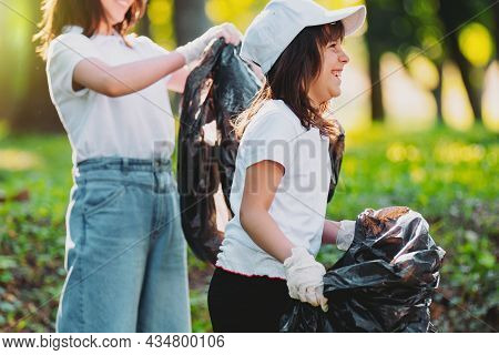 Side View Photo Of A Happy Young Girl In White Cap And T-shirt Wearing Gloves Keeping The Garbage Ba