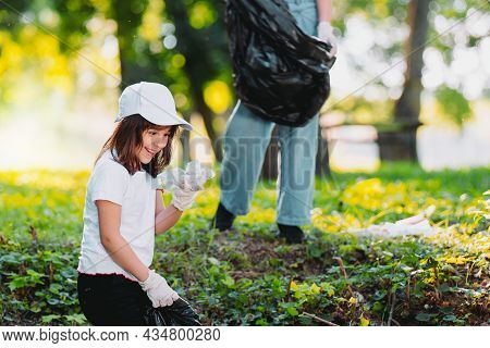 Happy Young Girl Sitting On Her Knees Down On The Ground Wearing White Cap And T-shirt In Protective