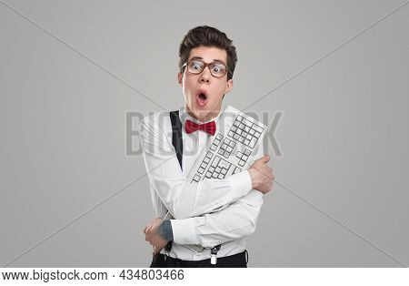 Astonished Young Man In Glasses Embracing Computer Keyboard And Looking Away While Working On Code A