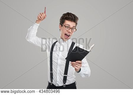 Happy Clever Young Businessman In Formal Clothes And Nerdy Glasses Holding Pen In Raised Hand And Lo