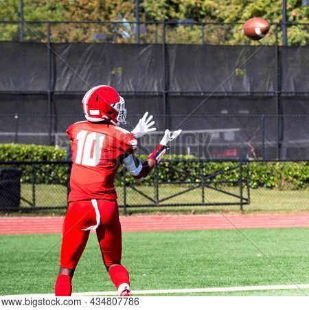A High School Football Wide Receiver Has His Hands Out To Catch The Fooball Wich Is In The Air For A