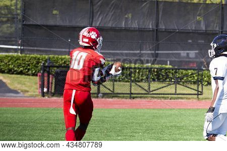 A High School Fottball Player Catching A Pass In The End Zone For A Touchdown With A Dejected Defend