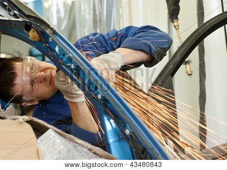 professional repairman worker in automotive industry grinding metal body car with sparks