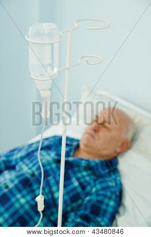 Adult patient lying on bed during intravenous injection by dropping bottle in hospital clinic for