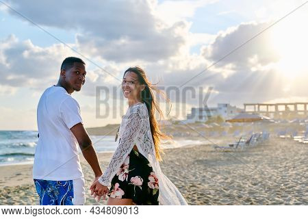 Portrait Of Happy Young Multiethnic Couple Holding Hands On The Seashore