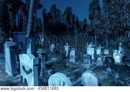 Cemetery In Forest On Halloween, Scary Graveyard With Mist And Bats At Creepy Night. Stone Graves In