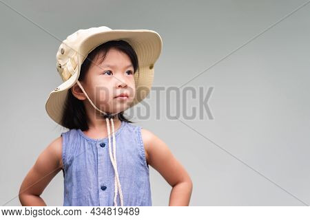 Portrait Of Cute Asian Child Looking Up. Little Girl Wearing Cream Colored Hat, Looks Like A Hiking