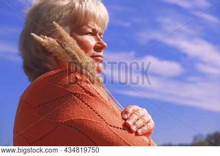 Portrait Of A Pensive Senior Woman In The  Park. Lady Contemplating The Future And Looking Aside Pen