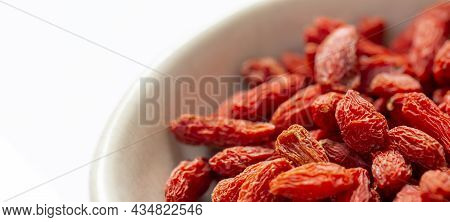 White Bowl Of Red Dried Goji Berries Isolated On White Background And Copy Space. Close Up.
