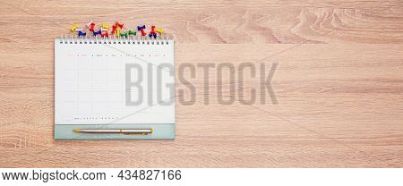 The Top View Desk Or Wooden Table Top And Blank Calendar With Office Equipment For Working Area Empt