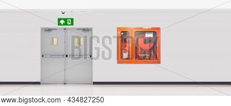Green Emergency Fire Exit Sign Or Fire Escape On Ceiling For Doorway Or Door Exit With Fire Hose Cab