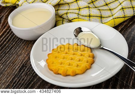 Checkered Napkin, Glass Bowl With Condensed Milk, Teaspoon With Condensed Milk And One Cookie In Whi