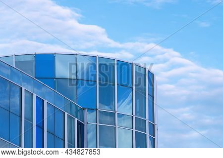 Low Angle View Of Modern Blue Glass Office Building Against White Clouds In Blue Sky Background, Man