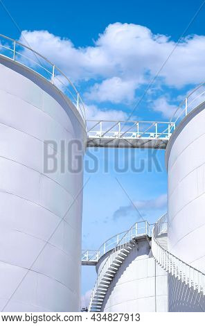 Low Angle View Of The Old White Fuel Tanks With Spiral Staircase Against Blue Sky Background In Vert