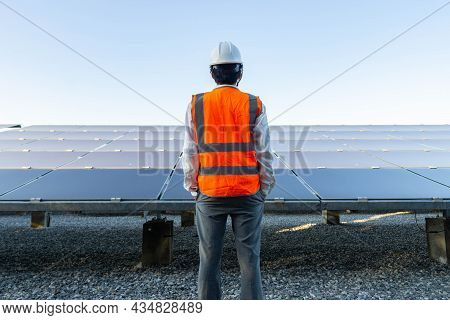 Engineer, Wearing An Orange Reflective Shirt, Looks At The Solar Panel, Alternative Energy To Conser
