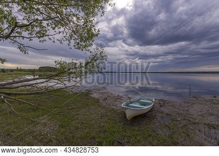 Evening Landscape On The Lake In Early Spring. The Dramatic Sky Is Reflected In The Water.
