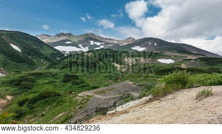 The Mountain Slopes Are Covered With Green Vegetation. In Some Places There Is Melted Snow. Tiny Fig