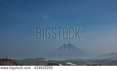 A Beautiful Conical Volcano With Snow-covered Slopes Against A Blue Sky With Light Clouds. Copy  Spa