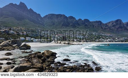 Turquoise Waves Of The Atlantic Ocean Foam On A Sandy Beach. There Are Boulders On The Shore. City H