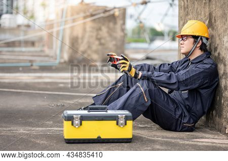 Asian Maintenance Worker Man Holding Red Aluminium Spirit Level Tool Sitting With Tool Box Taking A