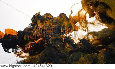 Abstract Background. Drops Of Black And Orange Ink In Water. Colored Acrylic Paints In Water. Black
