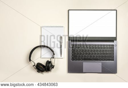 Top View On Laptop Blank Screen Blank Notepad And Headphones On White Table Background With Text Spa