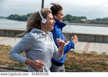 Two Young Happy And Self Loved Woman The Best Friends Jogging And Running Outdoor Near The River For