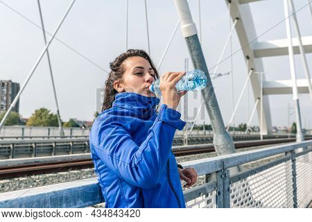 Young Beautiful Fitness Sporty Jogger Woman Standing On The Bridge Drinking Water For Hydration Afte