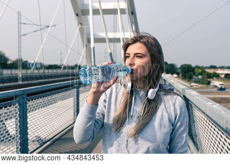 Young Beautiful Fitness Sporty Woman Standing On The Bridge Drinking Water For Hydration After Cardi