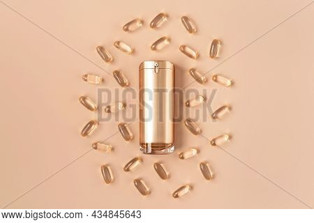 Beautiful Composition Of Gold Mockup Cosmetic Bottle And Vitamin Capsules On Pastel Background. Natu