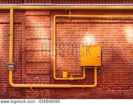 Red Brick Wall With Yellow Gas Pipes And Sunbeams. Old Wall With Sun Reflections. Old Building With