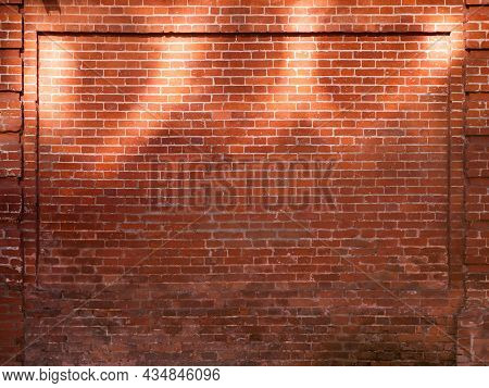 Red Brick Wall With Sunbeams. Old Wall With Sun Reflections At Upper Part. Old Building With Shabby