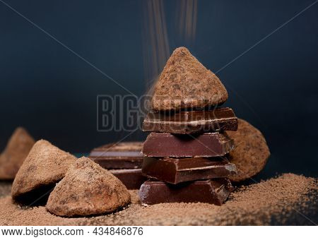 Chocolate Candy Truffle And Chocolate Pieces And Flying Cocoa Powder On A Dark Background