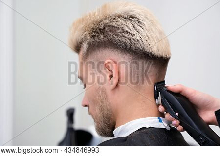 Haircut Process Of Blond Young Man With Hair Trimmer In Armchair In Barbershop Salon, Barbershop Con