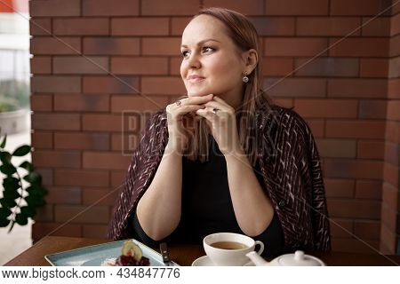 Close-up Portrait Of Smiling Woman Drinking Tea Alone. Lovable Lady Standing Near Brick Wall And Thi