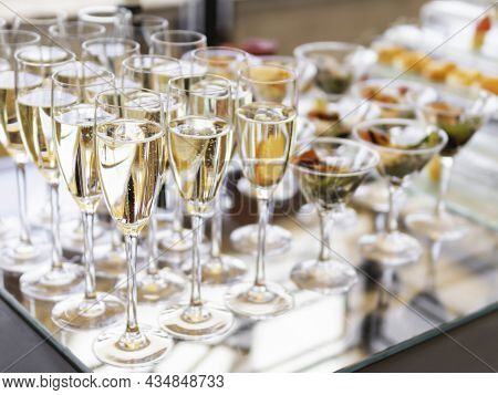 Champagne In Glasses, Bowls Of Snacks On A Shiny Glass Table. Buffet Table, Served For A Banquet. Ca