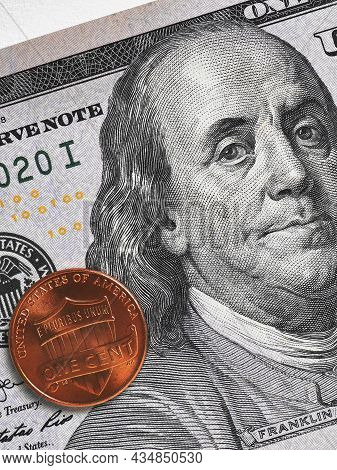 Us Money: 100 Dollar Bill And Penny (1 Cent) Lie On A Light Surface. American Currency And Economy.