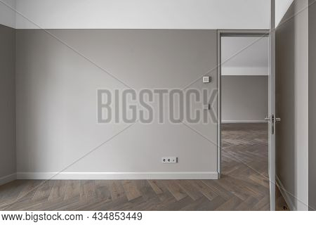 Simple Modern Beige-grey Wall With Grey Light Switch And Grey Socket In The Empty Room With Open Doo