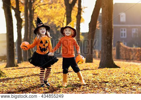 Kids Trick Or Treat On Halloween. Children In Black And Orange Witch Costume And Hat Play With Pumpk