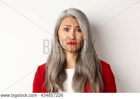 Close Up Of Sad And Unhappy Asian Senior Woman Sulking, Frowning And Looking Jealous At Camera, Stan