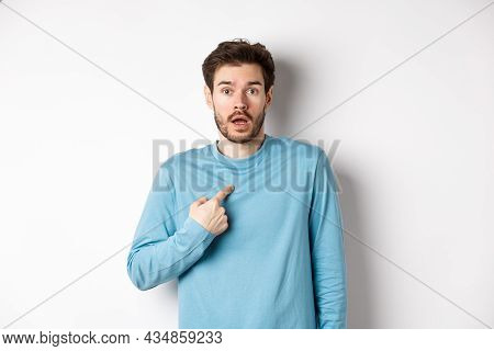 Surprised Young Man Gasping And Pointing At Himself With Disbelief, Being Chosen Or Named, Standing