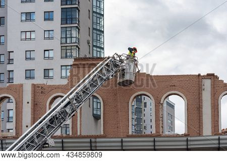 A Worker In A Construction Cradle Dismantles The Facade Of An Old Building.