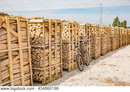Old Rusty Bike Is Parked Near Stacks Of Firewood For Industrial. Piles Of Firewood. Firewood Stacked